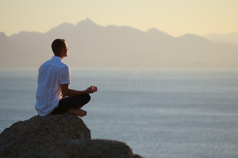 De zitting van de kerel op een rots in de lotusbloempositie royalty-vrije stock foto's