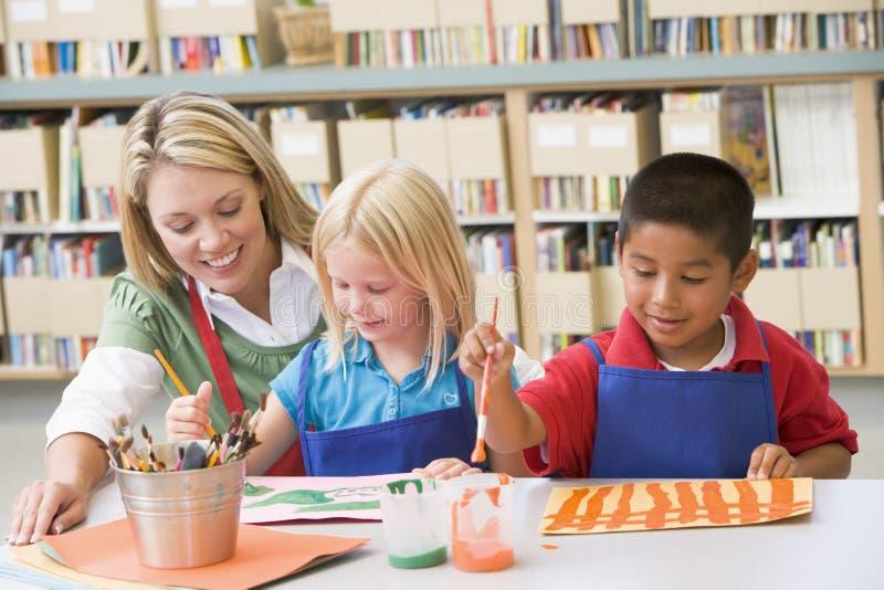 De zitting van de leraar met studenten in kunstklasse stock fotografie