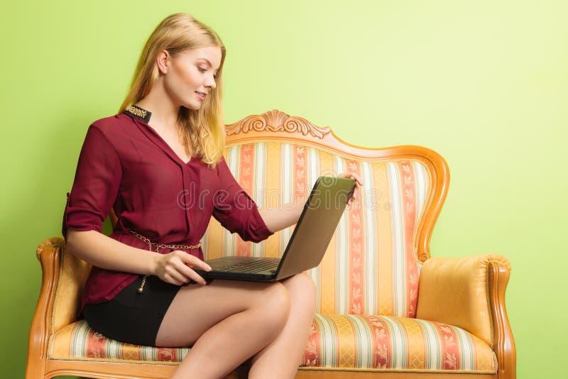 De zitting van de maniervrouw op bank die PC-laptop met behulp van royalty-vrije stock afbeelding