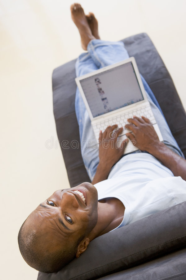 De zitting van de mens als voorzitter die laptop met behulp van stock fotografie