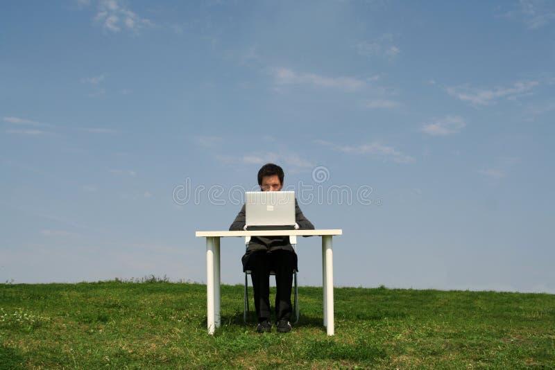 De zitting van de mens bij bureau, in openlucht stock foto