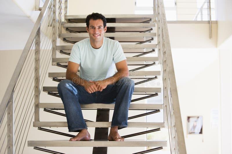 De zitting van de mens bij trap het glimlachen stock fotografie