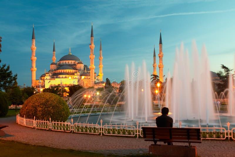 De zitting van de mens op een bank dichtbij van blauwe moskee stock afbeelding