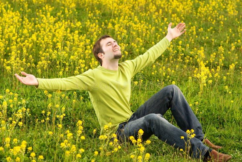 De zitting van de mens op een bloemgebied royalty-vrije stock afbeeldingen