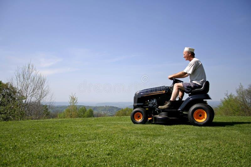 De zitting van de mens op een grasmaaier royalty-vrije stock foto