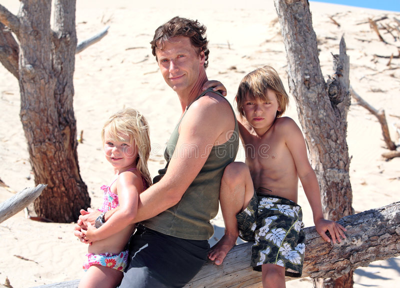 De zitting van de mens op een logboek met zijn zoon en dochter stock afbeeldingen