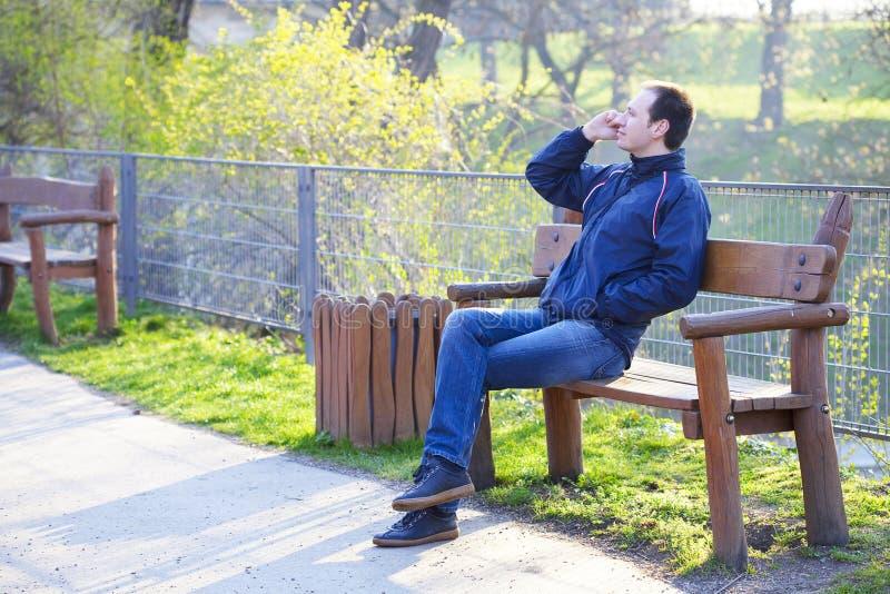 De zitting van de mens op een parkbank stock afbeelding