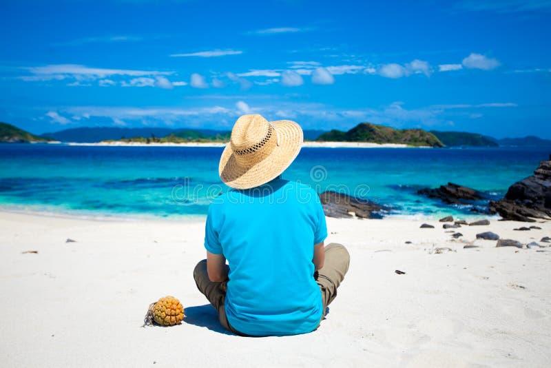 De zitting van de mens op het tropische eilandstrand royalty-vrije stock foto's