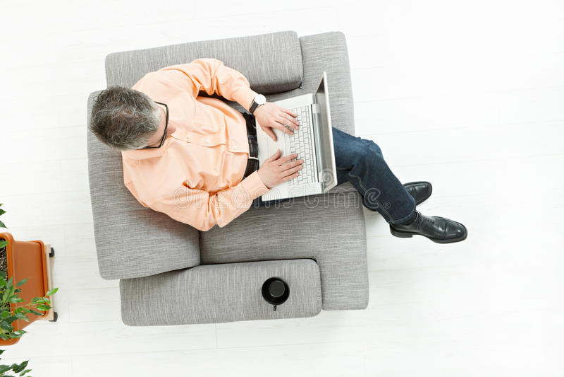 De zitting van de mens op laag en het werken aan laptop stock foto