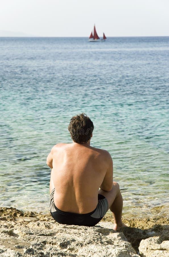 De zitting van de mens op strand stock foto's