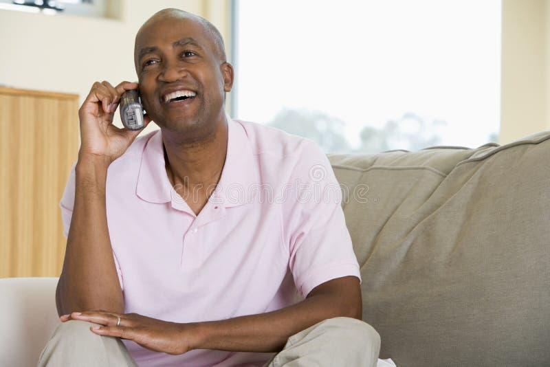 De zitting van de mens in woonkamer die telefoon met behulp van royalty-vrije stock foto