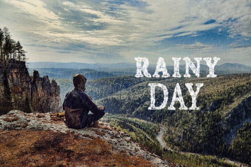 De zitting van de mensenwandelaar bovenop berg, het is nat slecht weer Het regenachtige dag van letters voorzien gemaakt van wolk stock fotografie