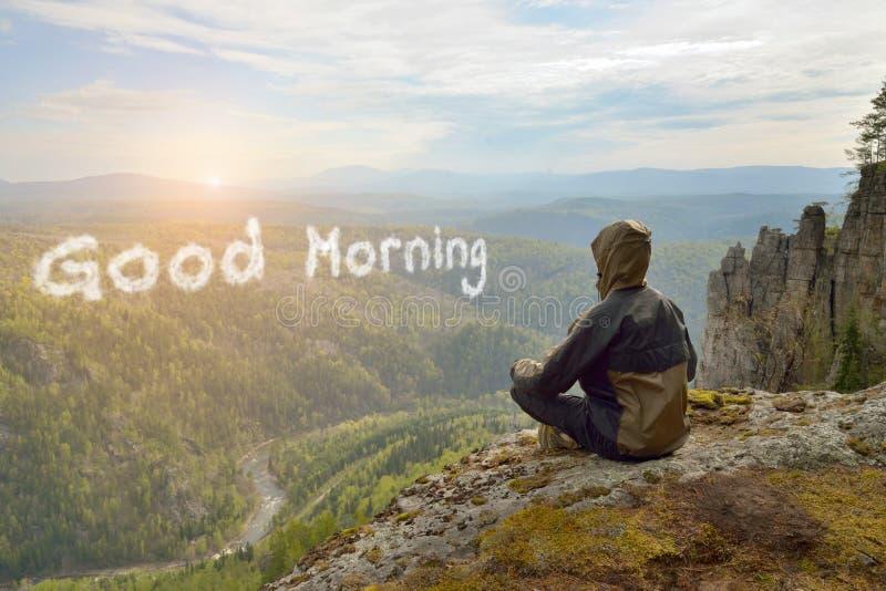 De zitting van de mensenwandelaar bovenop de zonsopgang van de bergvergadering, Goedemorgen het van letters voorzien in vorm van  royalty-vrije stock fotografie