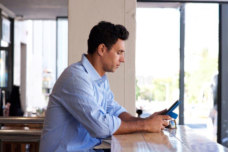 De zitting van de middenleeftijdsmens en het bekijken tablet stock afbeelding