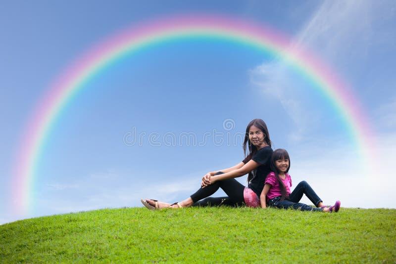 De zitting van de moeder en van de dochter samen op het gras royalty-vrije stock afbeeldingen