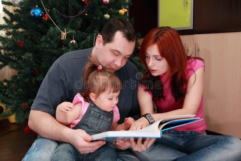 De zitting van de moeder, van de vader en van de dochter en leest boek stock afbeelding