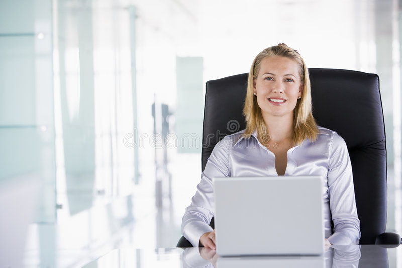 De zitting van de onderneemster in bureau met laptop stock foto