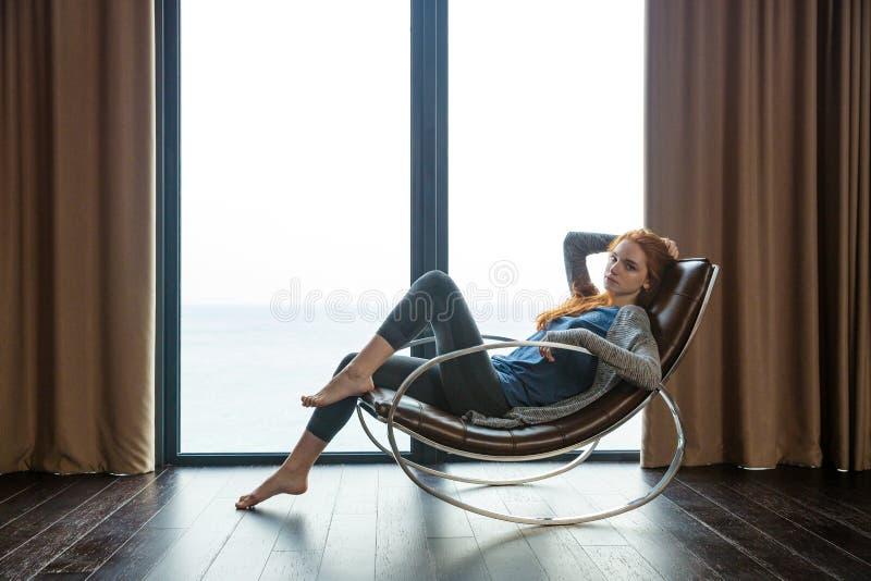 De zitting van de roodharigevrouw op schommelstoel stock fotografie