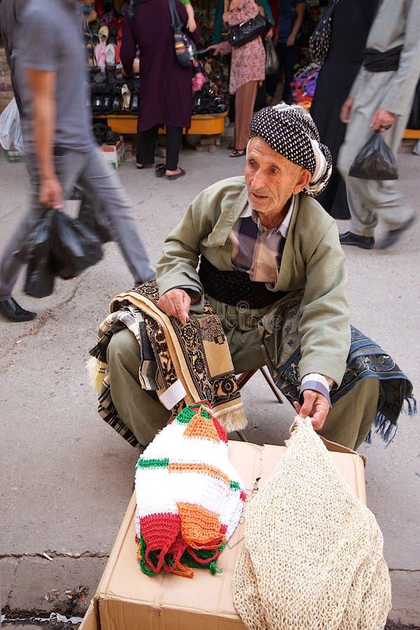 De zitting van de tapijtwerkkleinhandelaar in het midden van overvolle straat in bazaarmarkt. Irak. Midden-Oosten. royalty-vrije stock afbeelding