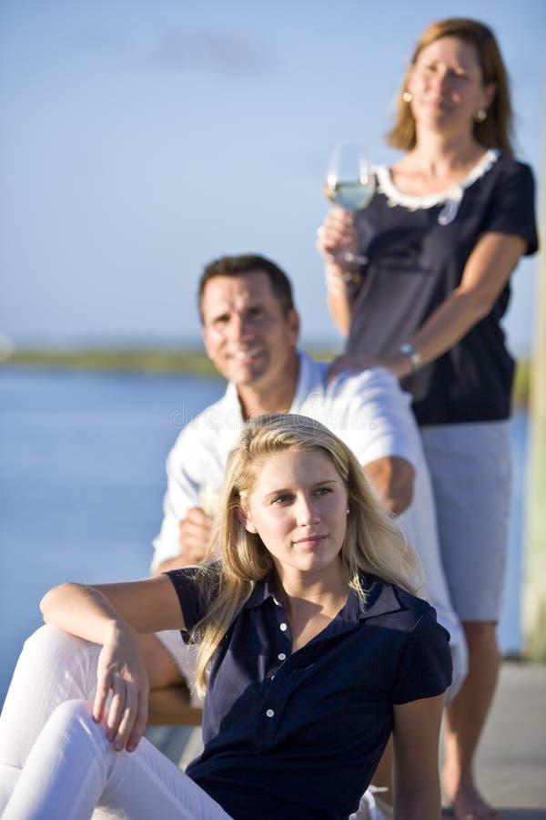 De zitting van de tiener op dok door water met ouders royalty-vrije stock afbeeldingen