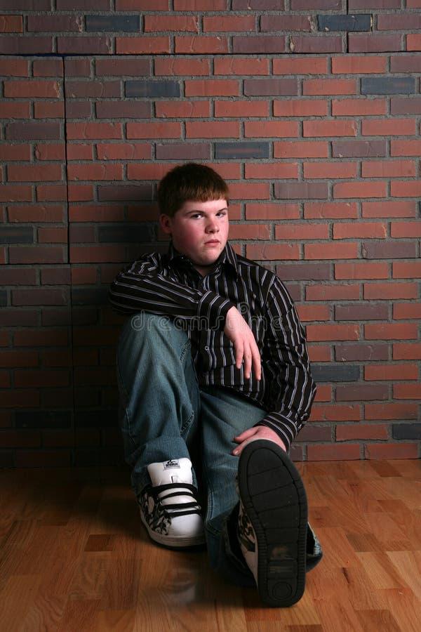 De zitting van de tiener op vloer royalty-vrije stock fotografie