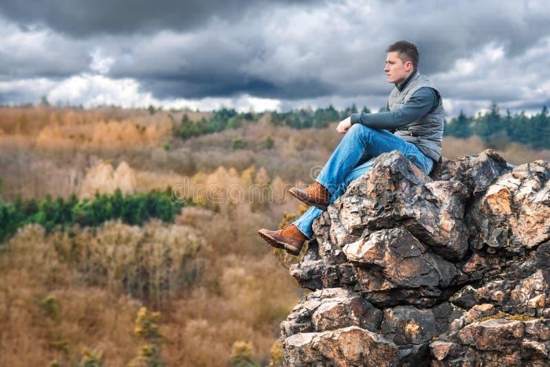De zitting van de toeristenwandelaar op de rots in berg royalty-vrije stock foto