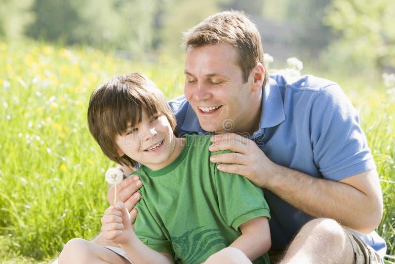 De zitting van de vader en van de zoon in openlucht royalty-vrije stock afbeeldingen