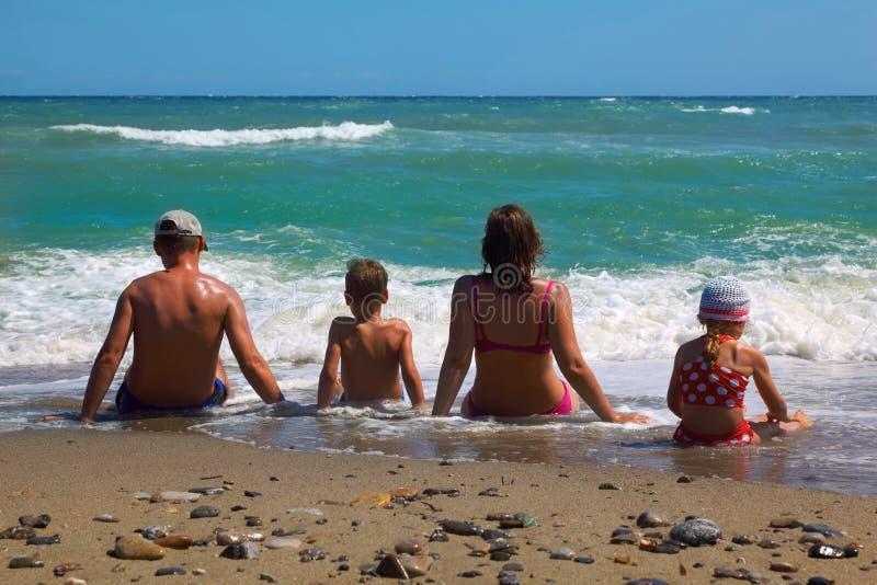 De zitting van de vader, van de moeder, van de zoon en van de dochter op strand royalty-vrije stock foto