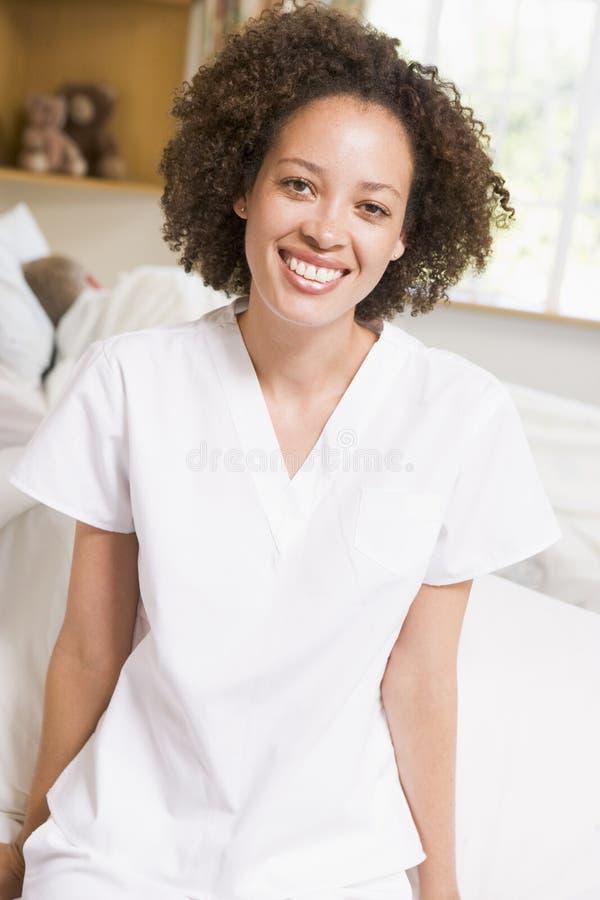 De Zitting van de verpleegster op het Bed van het Ziekenhuis stock afbeelding