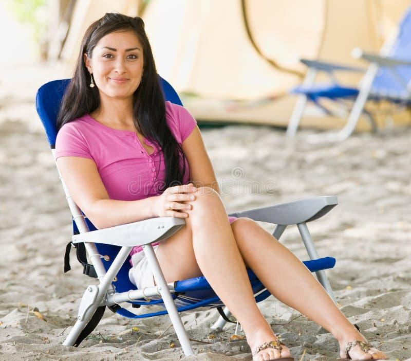 De zitting van de vrouw als voorzitter bij kampeerterrein stock foto's