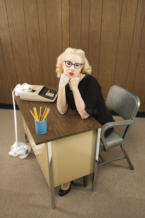 De zitting van de vrouw bij bureau royalty-vrije stock afbeelding