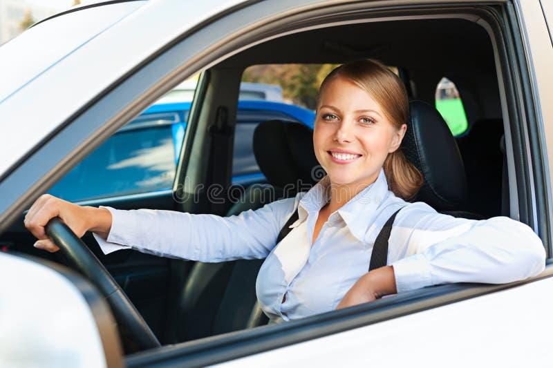 De zitting van de vrouw in de auto en het glimlachen royalty-vrije stock afbeeldingen