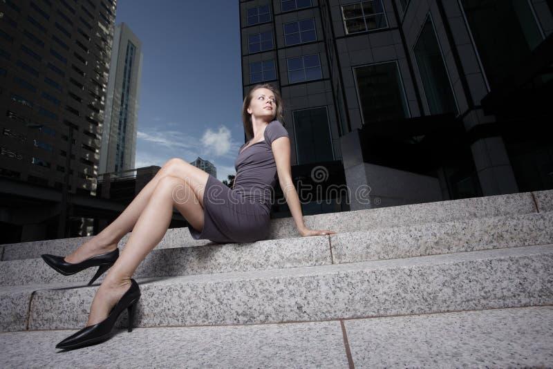 De zitting van de vrouw door een bureaugebouw royalty-vrije stock foto