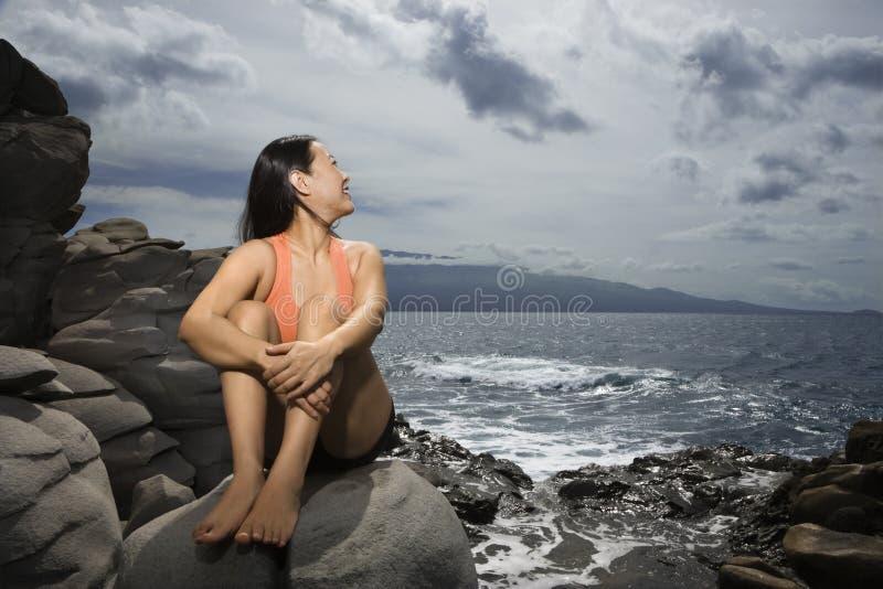 De zitting van de vrouw door oceaan royalty-vrije stock afbeeldingen