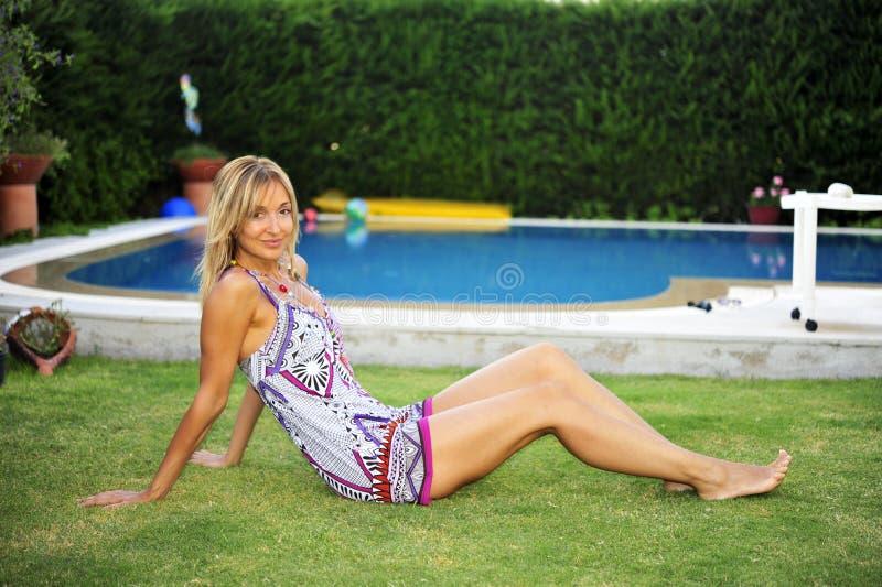 De zitting van de vrouw door pool royalty-vrije stock afbeeldingen