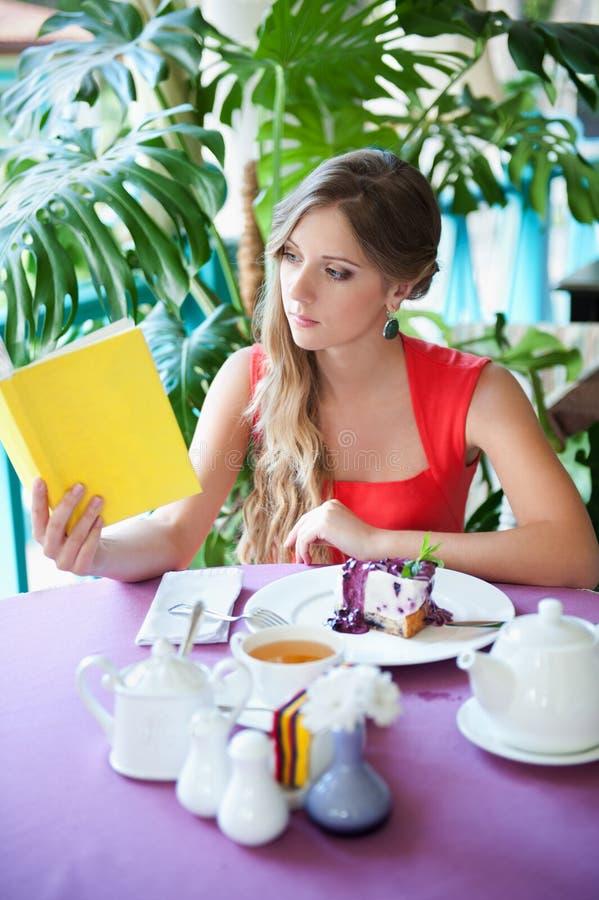 De zitting van de vrouw in koffie en lezing het boek stock fotografie