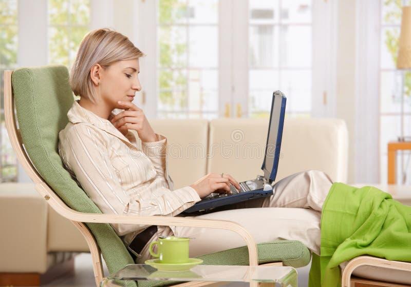 Vrouw die met computer thuis werken stock foto