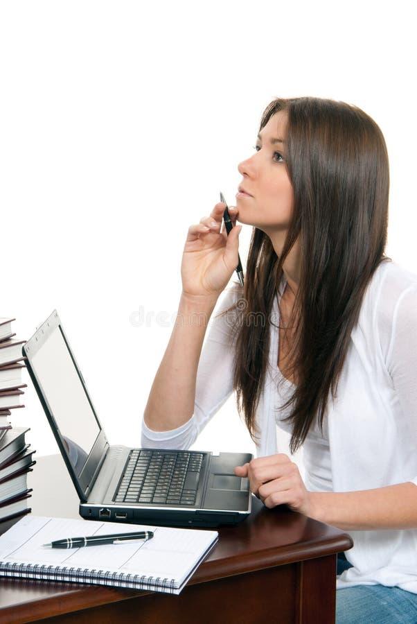 De zitting van de vrouw met laptop met in hand pen stock foto
