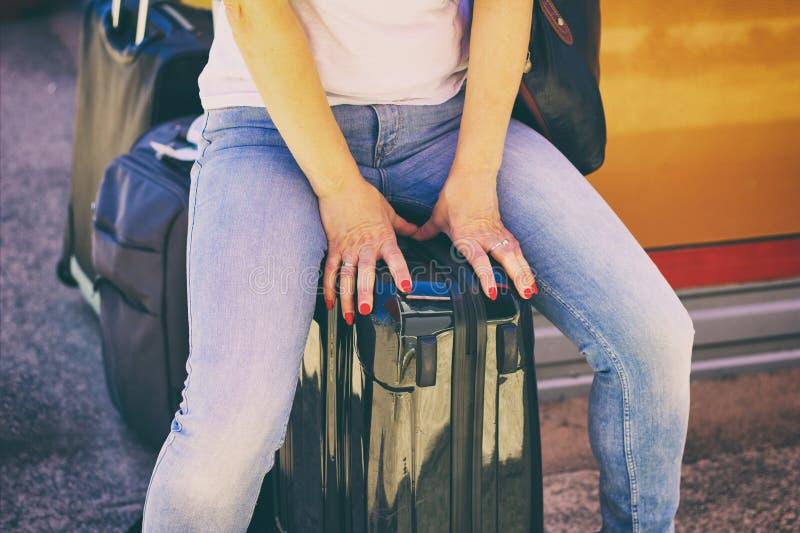 De zitting van de vrouw op bagage stock foto's