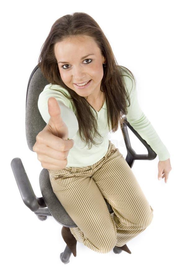 De zitting van de vrouw op de bureaustoel, die o.k. toont royalty-vrije stock foto