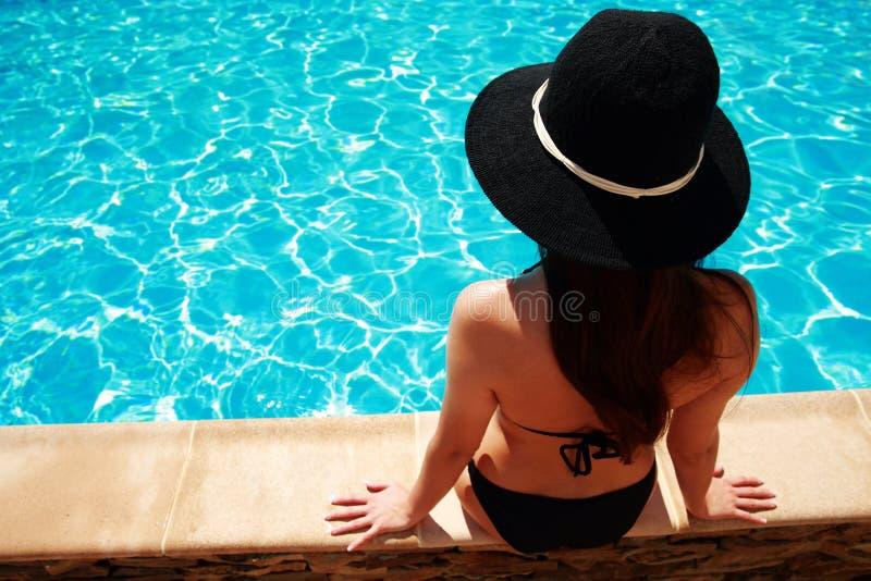 De zitting van de vrouw op de richel van de pool royalty-vrije stock afbeeldingen