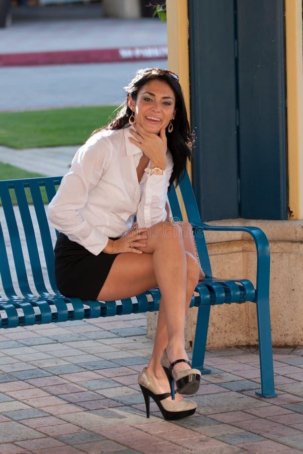 De zitting van de vrouw op een parkbank royalty-vrije stock afbeeldingen