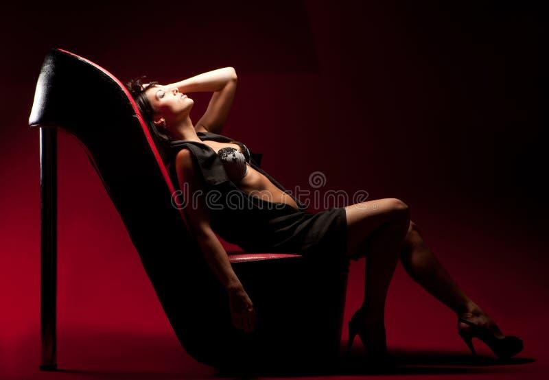 De zitting van de vrouw op een stoel royalty-vrije stock afbeeldingen