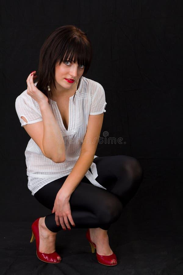 De zitting van de vrouw op een zwarte achtergrond stock afbeeldingen