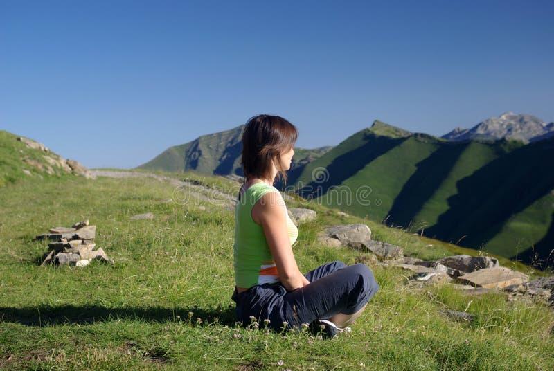 De zitting van de vrouw op gras in bergen het ontspannen royalty-vrije stock afbeelding