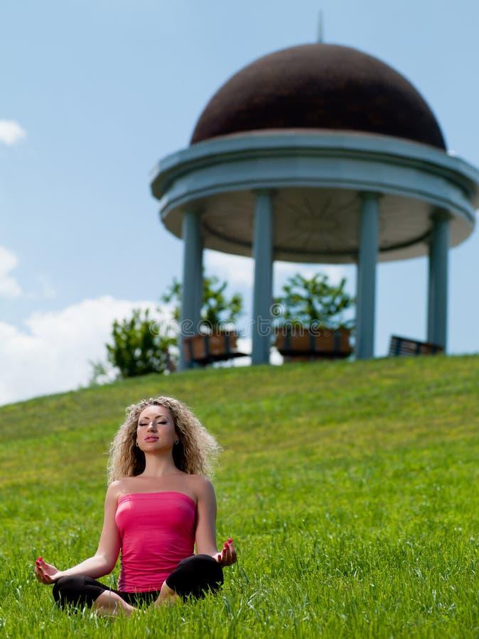 De zitting van de vrouw op het gras royalty-vrije stock foto