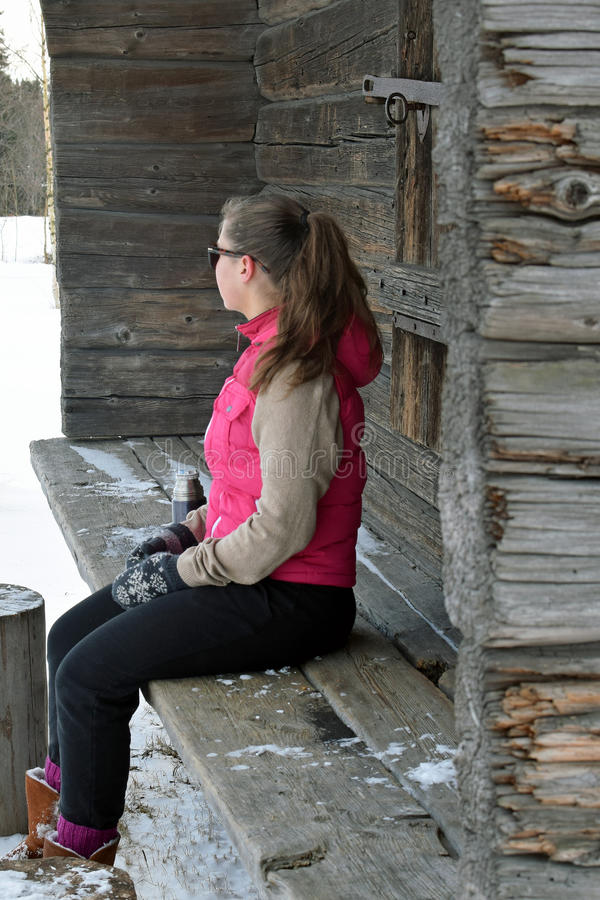 De zitting van de vrouw op houten bank stock foto's