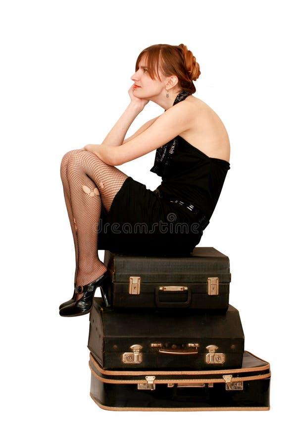 De zitting van de vrouw op koffers stock afbeeldingen