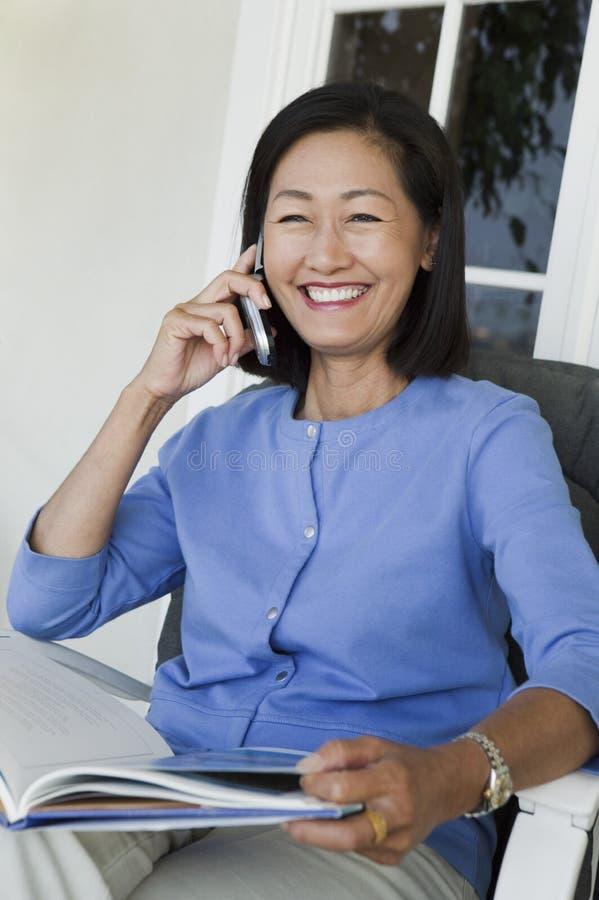 De zitting van de vrouw op leunstoel, die op mobiel spreekt stock fotografie
