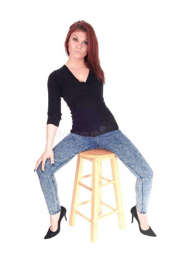 De zitting van de vrouw op staafstoel royalty-vrije stock afbeelding